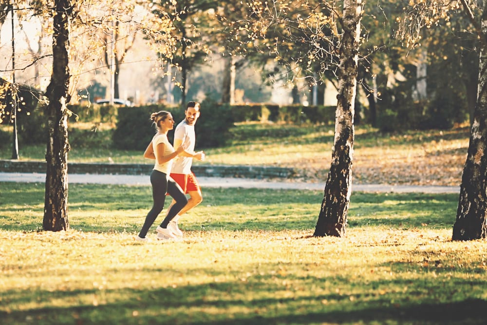 Couple on a run in a park near Cypress Pointe Apartments in Gilroy, California