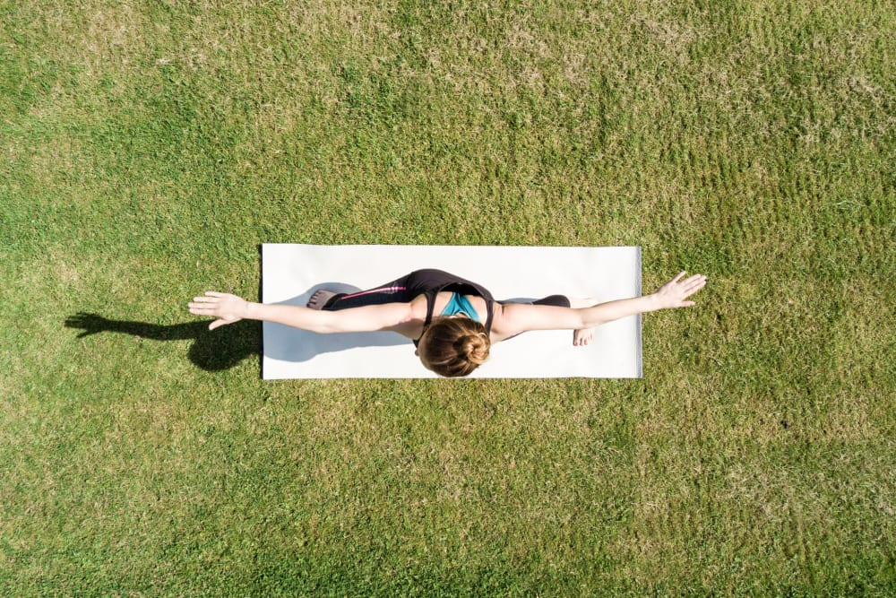 Resident doing yoga on the lawn at Greendale Apartments in Mountain View, California