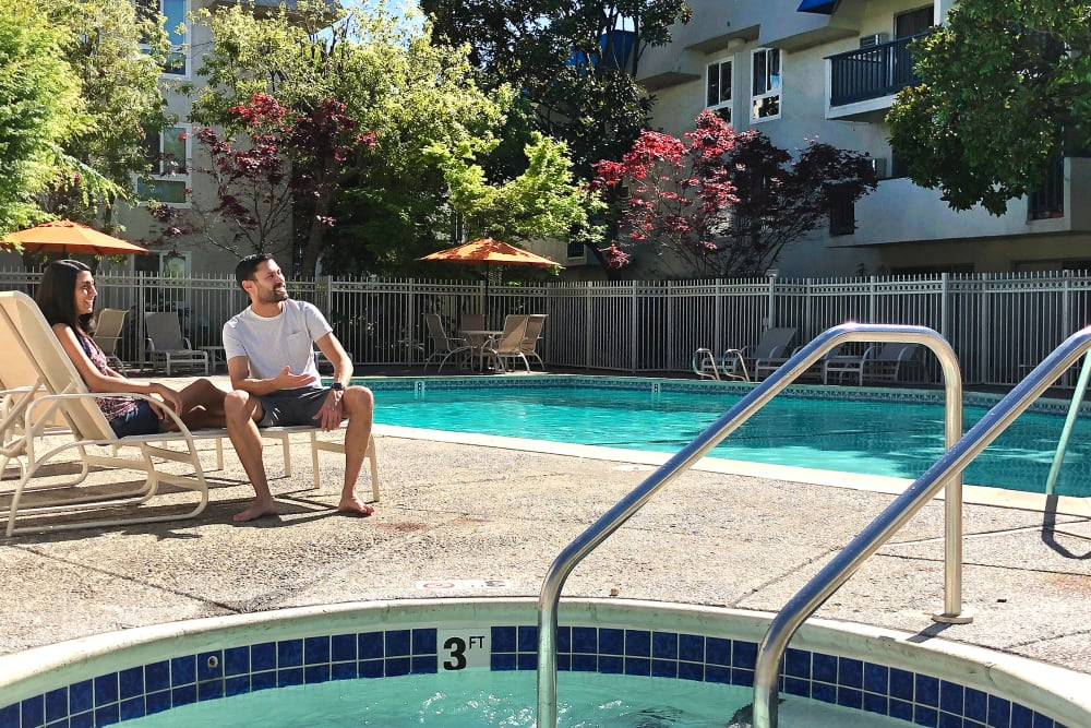Resident relaxing by the swimming pool at Newport Apartments in Campbell, California