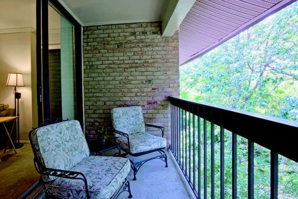 Comfortable chairs on a model home's private balcony at The Timbers at Long Reach Apartments in Columbia, Maryland