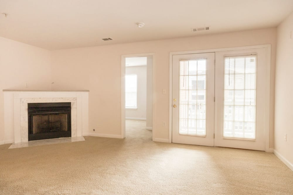Living room with a fireplace and patio access at Glade Creek Apartments in Roanoke, Virginia