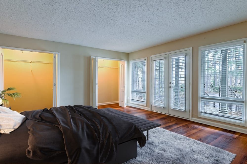 Bedroom with wood floors and large picture windows at The Lodge on the Chattahoochee Apartments in Sandy Springs, Georgia