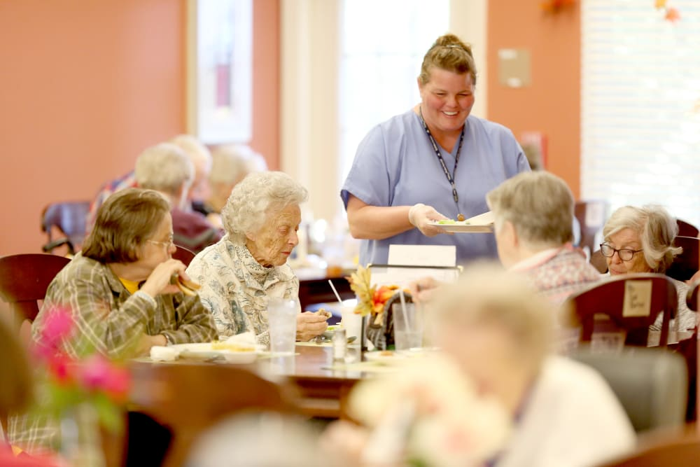 A staff member helping residents at mealtime at Providence Assisted Living.