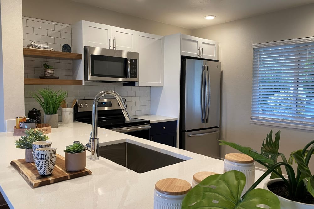 Quartz countertops and bright white cabinetry in the gourmet kitchen of a model home at Harbor Point Apartments in Mill Valley, California