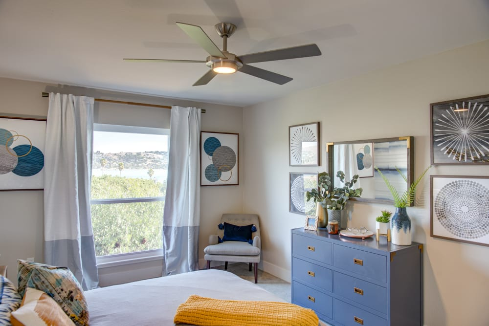 Ceiling fan and comfortable decor in the master bedroom of a model home at Harbor Point Apartments in Mill Valley, California