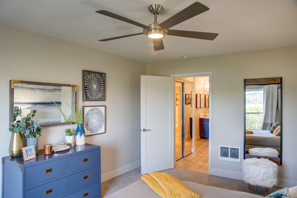 Cozy furnishings and a ceiling fan in a model home's master bedroom at Harbor Point Apartments in Mill Valley, California