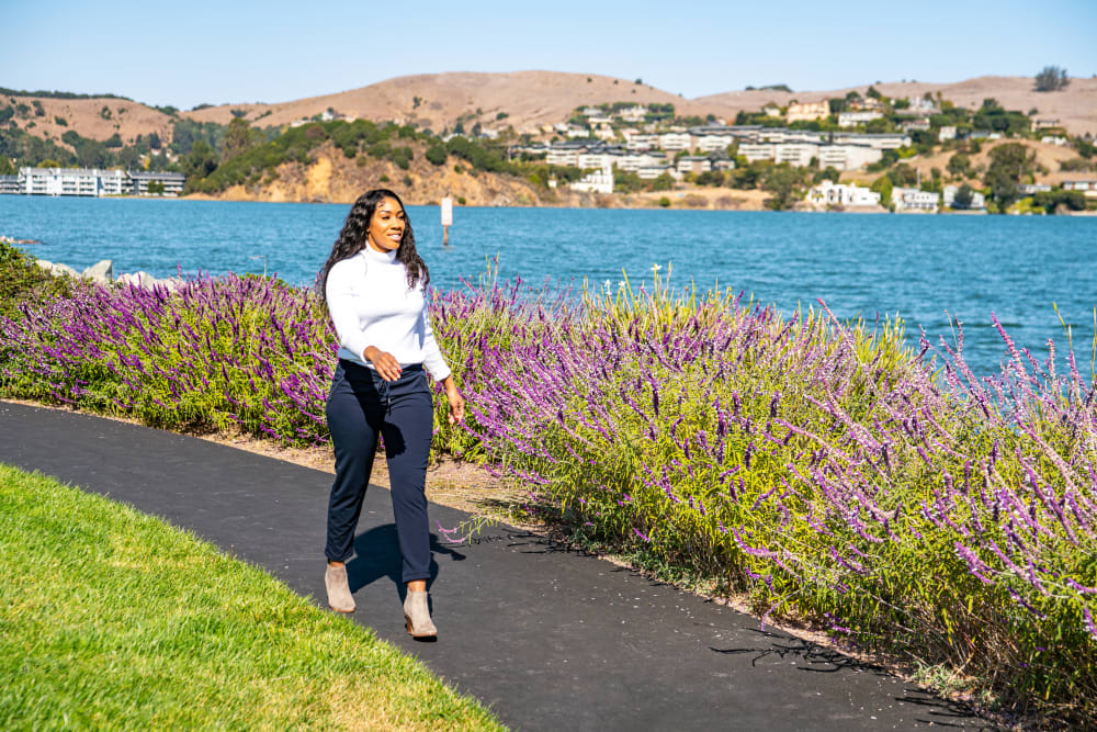 Resident walking along one of the flower-lined pathways next to the bay at Harbor Point Apartments in Mill Valley, California