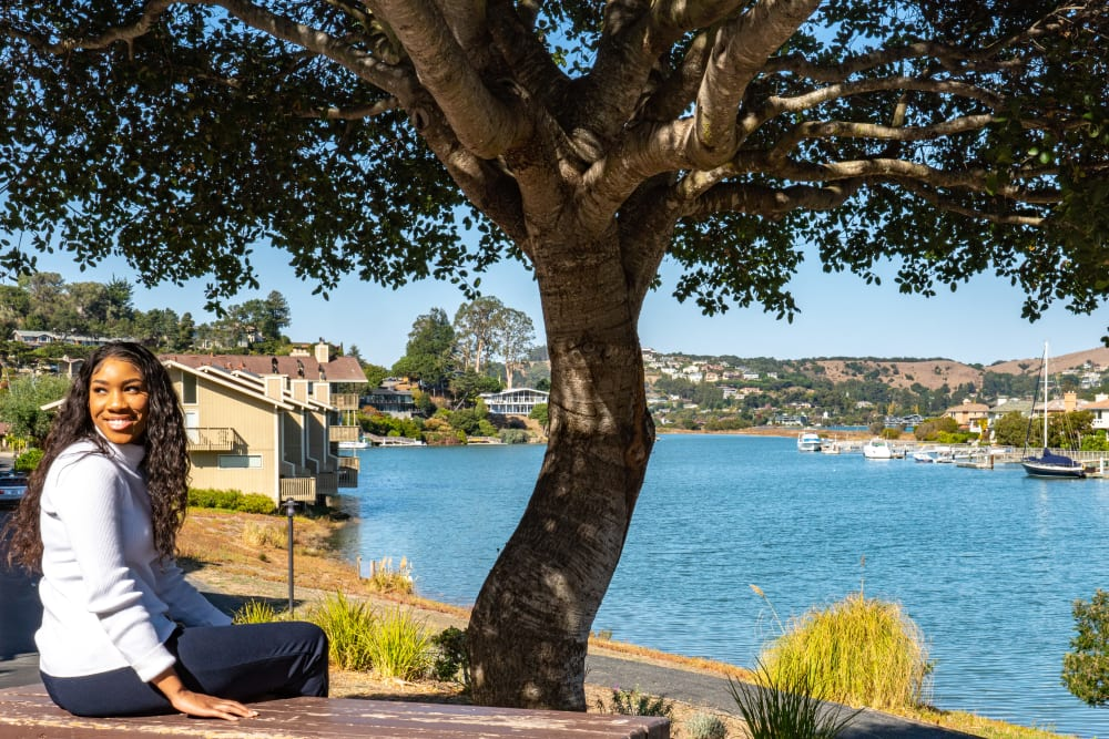 Resident taking a break from her walk by a mature tree near the bay at Harbor Point Apartments in Mill Valley, California