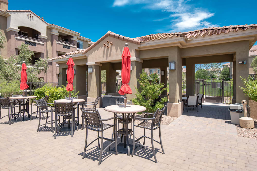 Tables with umbrellas and chairs in one of the well-maintained outdoor common areas at Broadstone Towne Center in Albuquerque, New Mexico