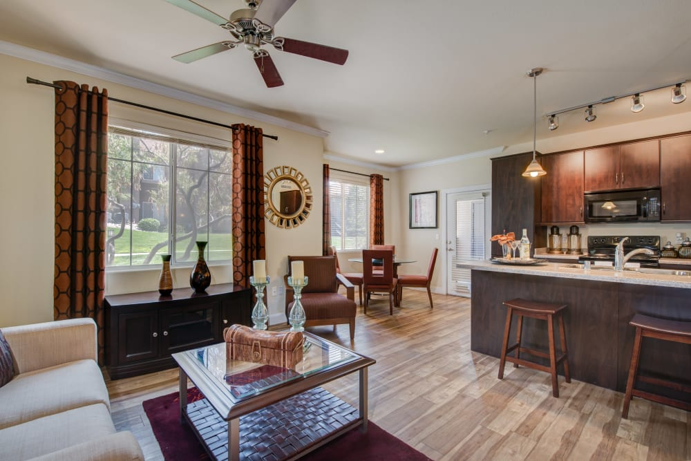Open-concept living area with hardwood floors and a ceiling fan in a model home at Broadstone Towne Center in Albuquerque, New Mexico
