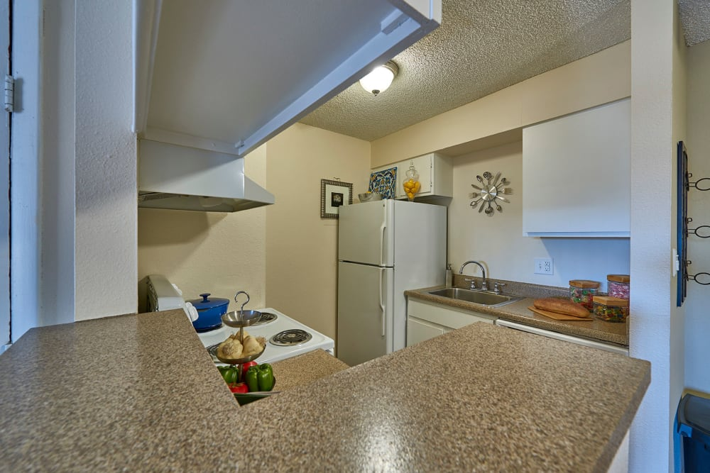 Kitchen with a breakfast bar at Hampden Heights Apartments in Denver, Colorado