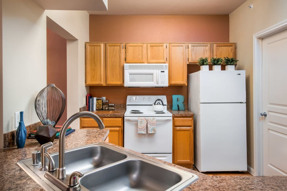 Dual-basin sink and bright white appliances in a model home's kitchen at Reserve at Pebble Creek in Plano, Texas