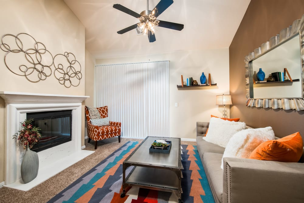 Fireplace and a ceiling fan in the well-furnished living area of a model home at Reserve at Pebble Creek in Plano, Texas