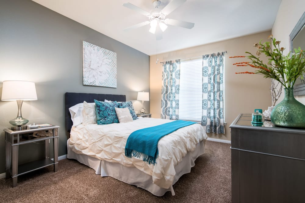 Bedroom with plush carpeting and an accent wall in a model home at Reserve at Pebble Creek in Plano, Texas