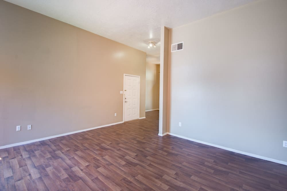 Large living room with wood-style flooring at Mesa Del Oso in Albuquerque, New Mexico