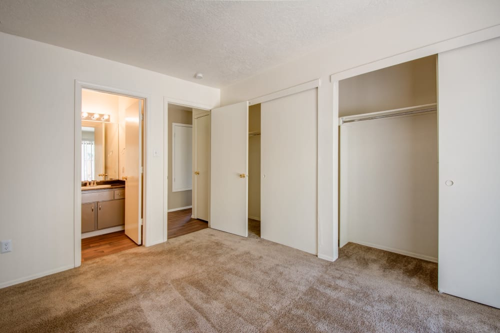 Large bedroom with plush carpeting and a closet at Mesa Del Oso in Albuquerque, New Mexico