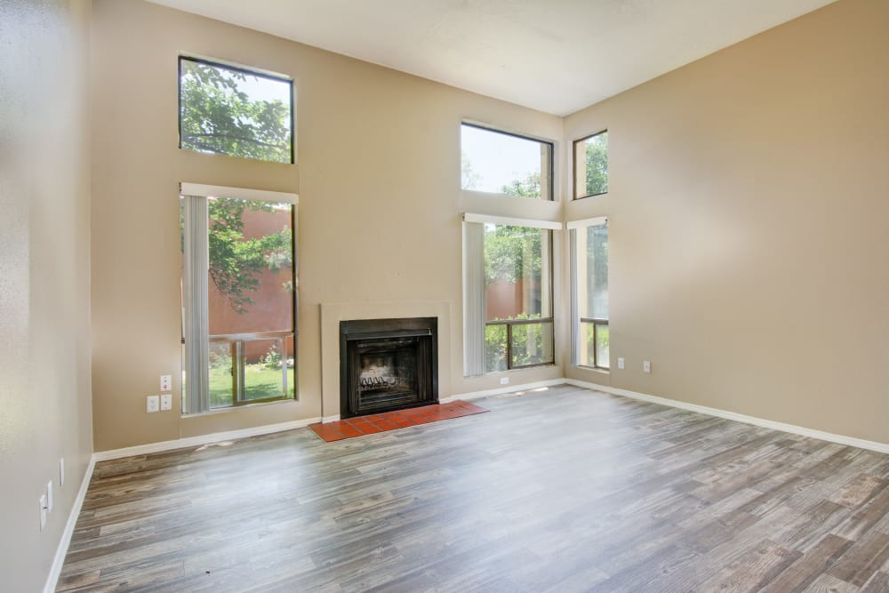 Living room with large windows and a fireplace at Mesa Del Oso in Albuquerque, New Mexico