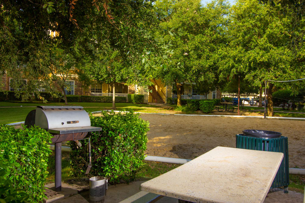 Barbecue area with gas grills near the volleyball court at The Lodge at River Park in Fort Worth, Texas
