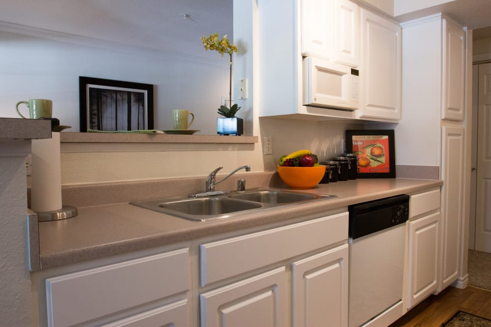 Granite countertops and bright white cabinetry in a model home's kitchen at The Lodge at River Park in Fort Worth, Texas