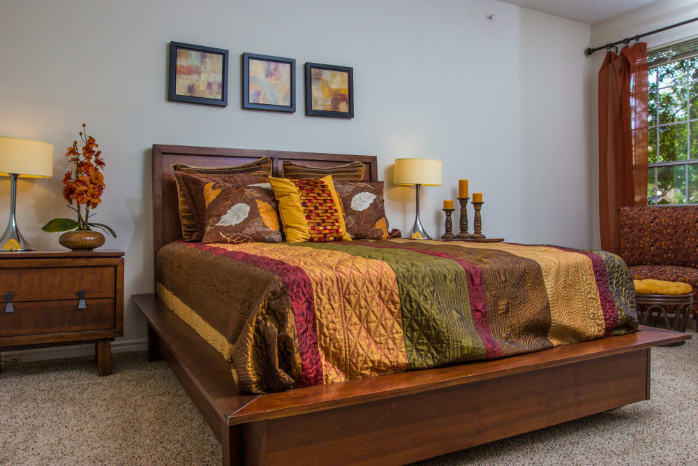 Well-furnished master bedroom with plush carpeting in a model home at The Lodge at River Park in Fort Worth, Texas