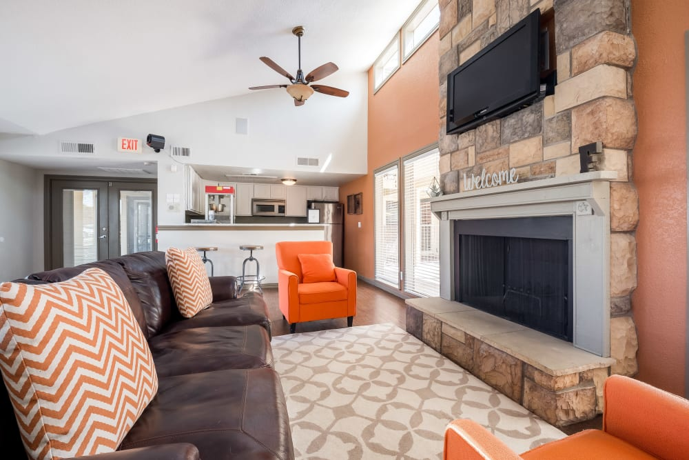 Resident lounge with a flat-screen TV and fireplace at The Fairway Apartments in Plano, Texas