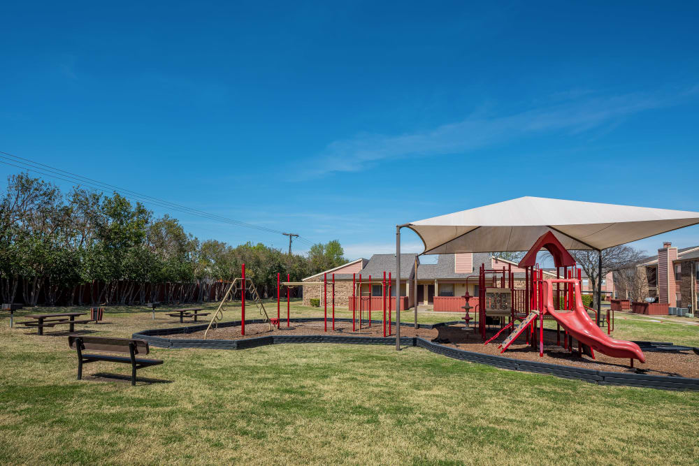 Children's playground with a sunsail at The Fairway Apartments in Plano, Texas