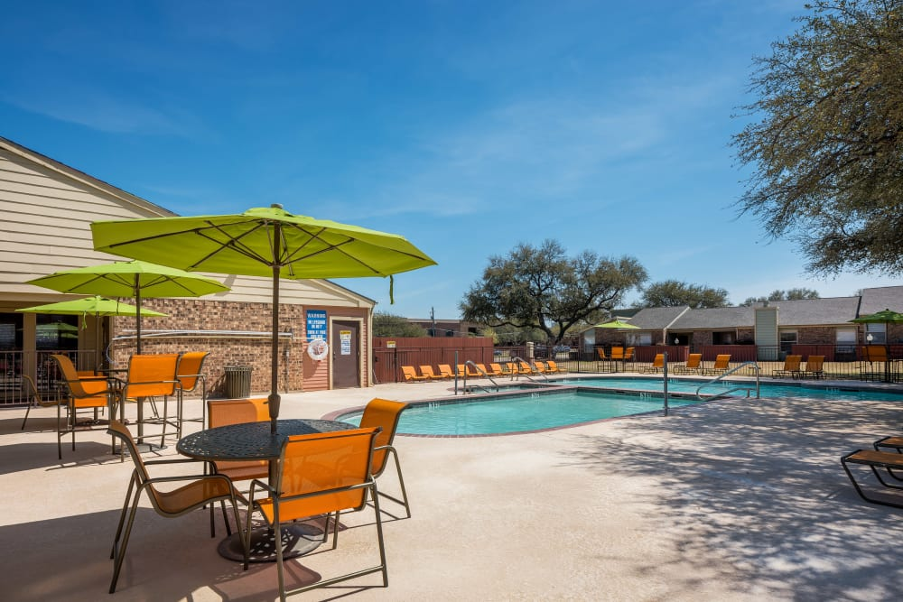 Poolside tables and chairs with umbrellas at The Fairway Apartments in Plano, Texas