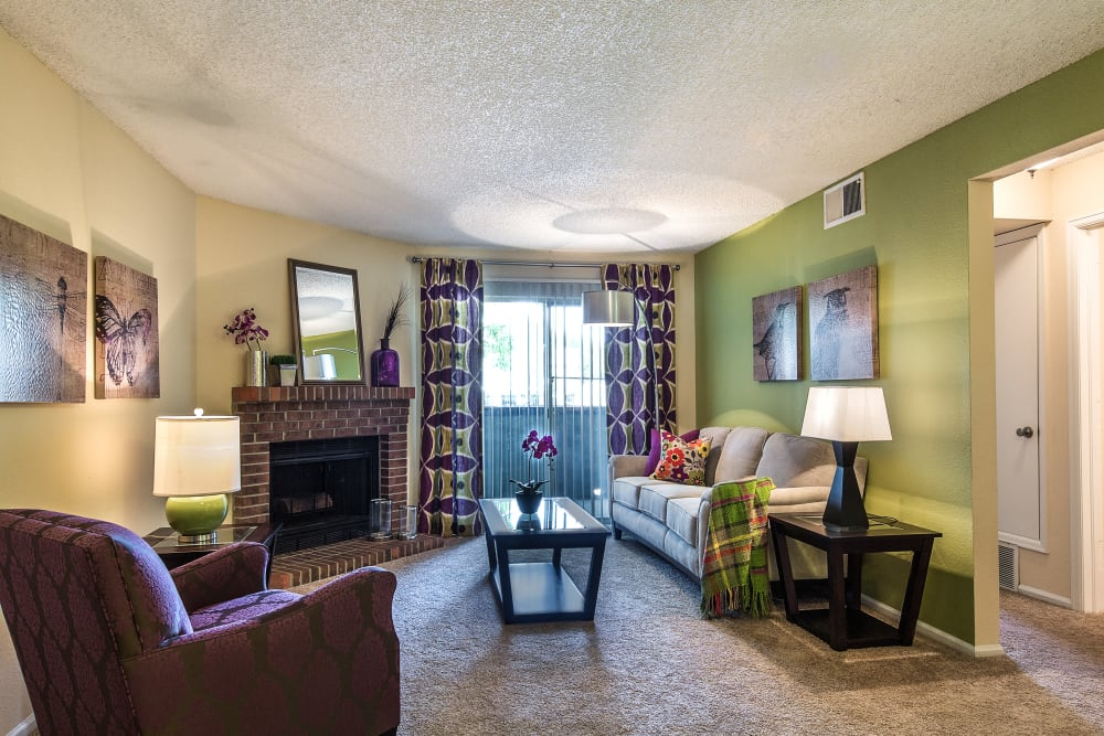 Fireplace and an accent wall in a model home's living area at Waterfield Court Apartment Homes in Aurora, Colorado