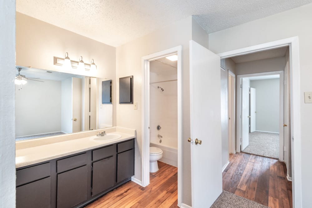 Large bathroom with plenty of cupboard space and a granite-style countertop in an apartment home at The Madison in Dallas, Texas