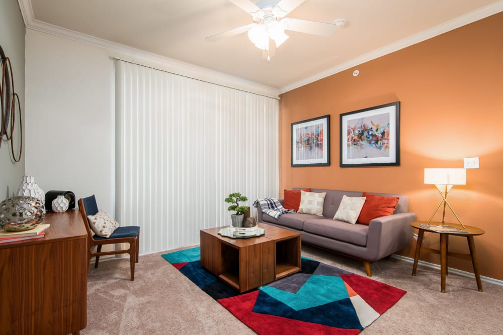 Ceiling fan and plush carpeting in a model home's living area at Rockbrook Creek in Lewisville, Texas