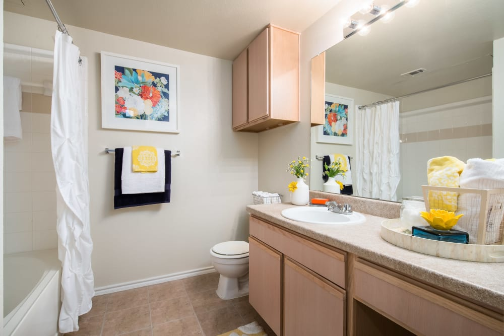 Large bathroom with a granite-style countertop and tile flooring in a model home at Rockbrook Creek in Lewisville, Texas