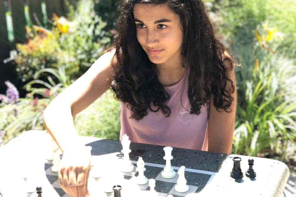 Girl playing chess outdoors at Village Green Apartments in Cupertino, California
