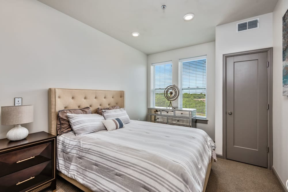 Resident bedroom with large windows at Anthology of Clayton View in Saint Louis, Missouri.