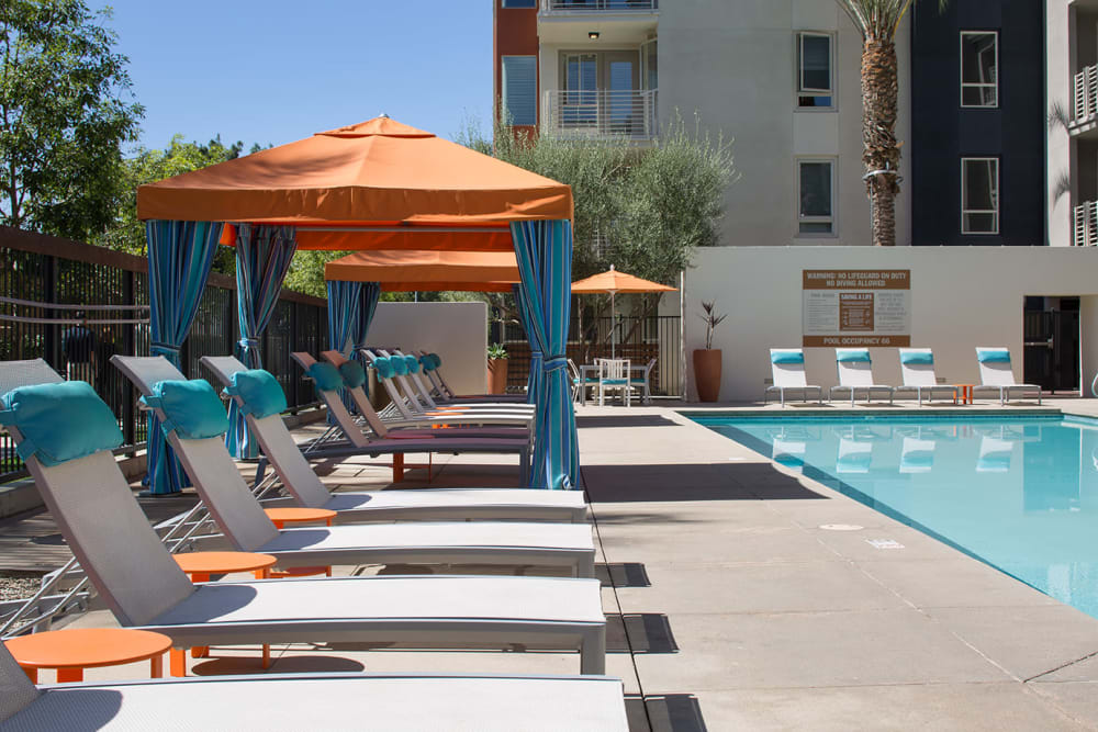 Chaise lounge chairs and shaded seating near the pool at Sofi Warner Center in Woodland Hills, California