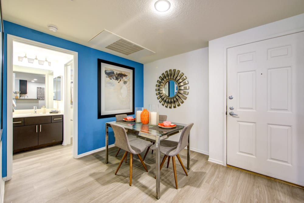 Dining nook with an accent wall and a guest bathroom nearby in a model home at Sofi at 3rd in Long Beach, California