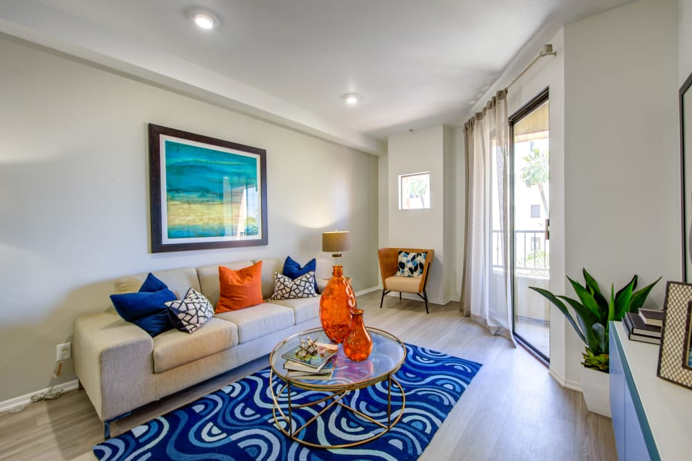 Living area with a sliding glass door to the private balcony outside a model home at Sofi at 3rd in Long Beach, California