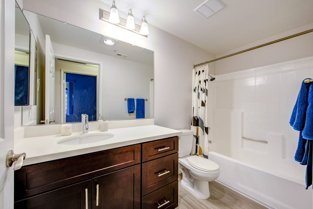 Tiled shower and hardwood flooring in a model home's bathroom at Sofi at 3rd in Long Beach, California