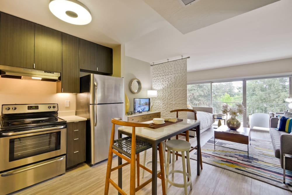 Modern kitchen with an island and stainless-steel appliances in a model studio apartment at Mia in Palo Alto, California