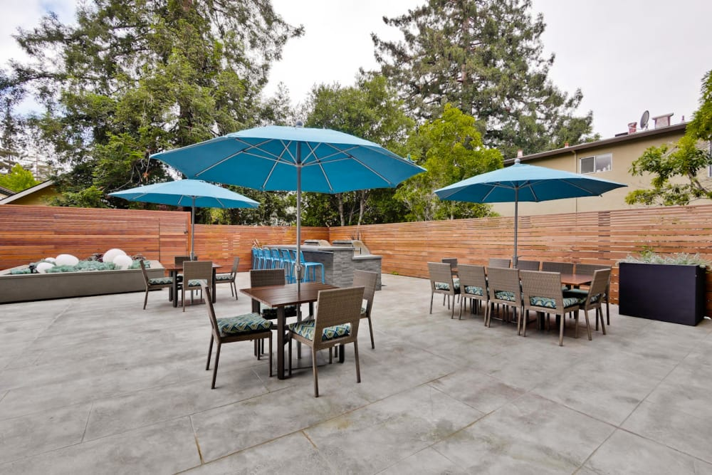 Tables with umbrellas and plenty of seating at one of the outdoor common areas at Mia in Palo Alto, California