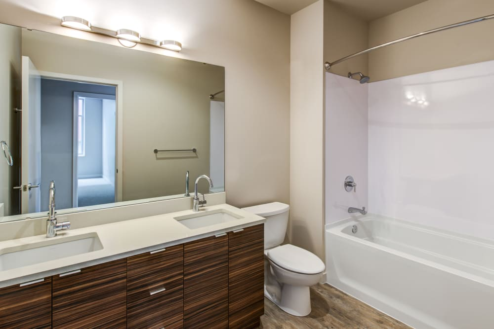 Well-lit bathroom with a large vanity mirror and dual sinks in a model home at Verse Seattle in Seattle, Washington