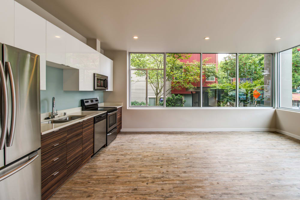 Hardwood flooring in the open-concept kitchen and living areas of a model home at Verse Seattle in Seattle, Washington