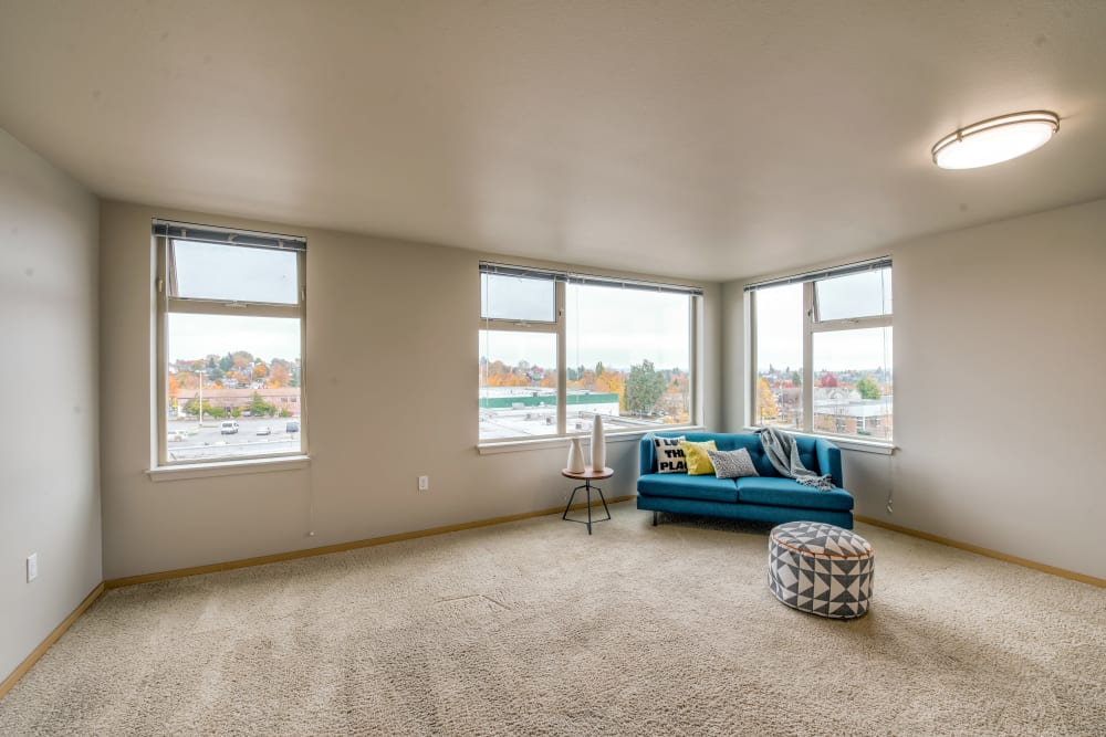 Open layout with plush carpeting in the living area of a model home at Verse Seattle in Seattle, Washington