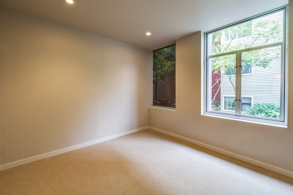 Large master bedroom with plush carpeting and large bay windows in a model home at Verse Seattle in Seattle, Washington