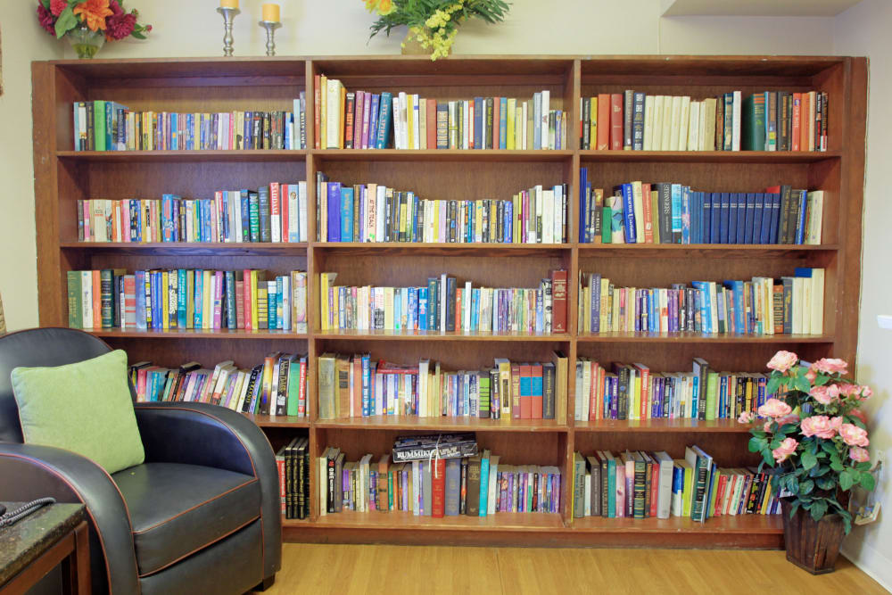A fully stocked bookshelf with comfortable seating nearby at Bradenton Oaks in Bradenton, Florida