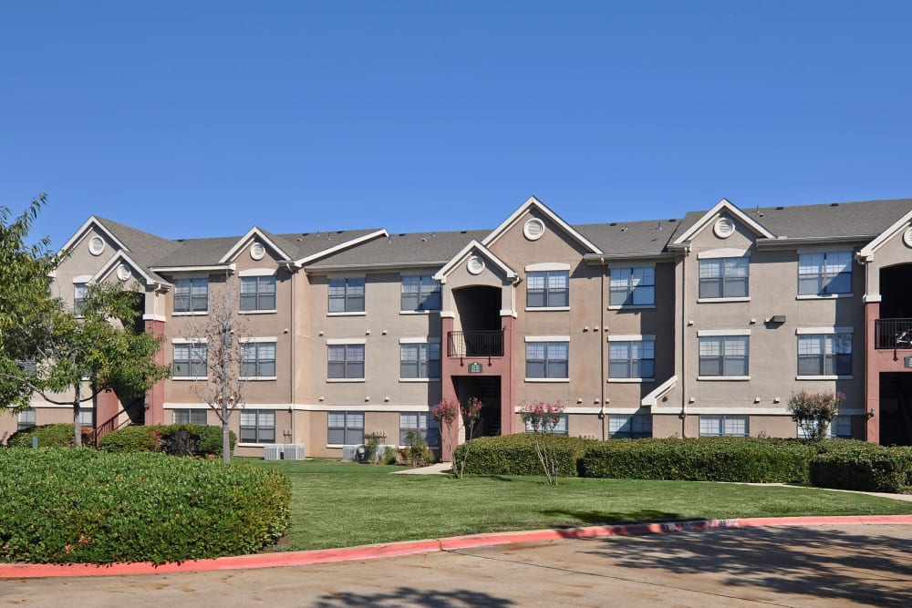 Professionally maintained landscaping outside resident buildings at Arbrook Park Apartment Homes in Arlington, Texas