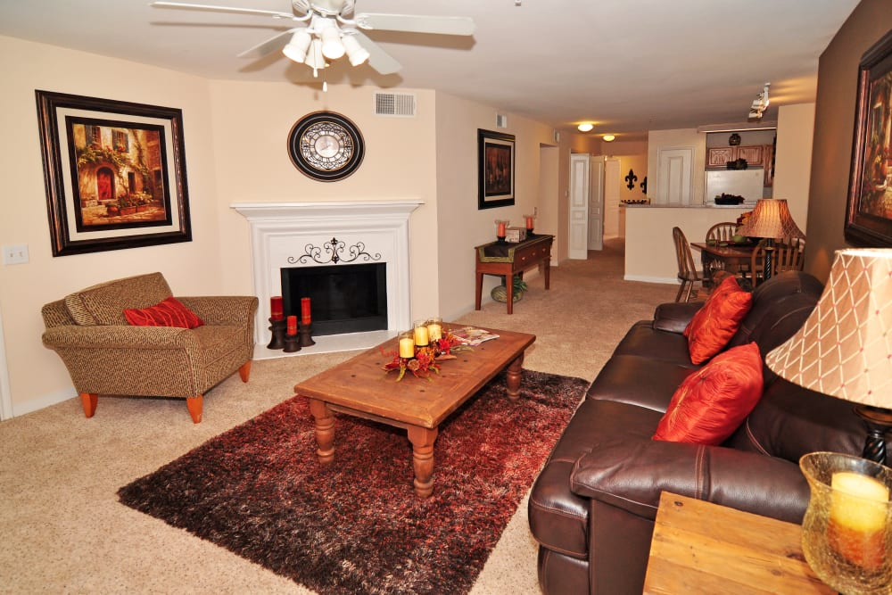 Spacious living area with a fire place and a ceiling fan in a model home at Arbrook Park Apartment Homes in Arlington, Texas