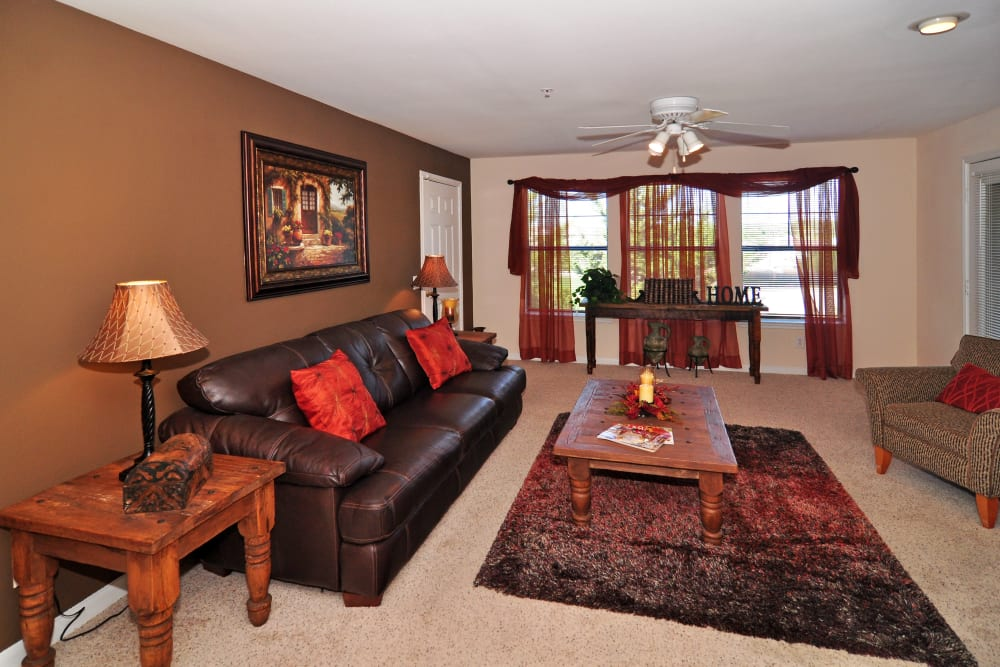 Classic furnishings and an accent wall in the living area of a model home at Arbrook Park Apartment Homes in Arlington, Texas