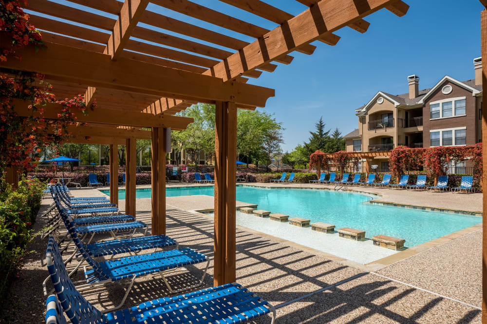 Pergola providing shade for lounge chairs near the pool at Arbrook Park Apartment Homes in Arlington, Texas
