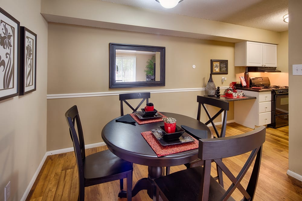 Dining area with hardwood flooring looking into the kitchen of a model home at Oxford Hills in St. Louis, Missouri