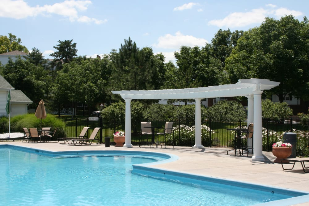 Pergola and chaise lounge chairs next to the pool at Oxford Hills in St. Louis, Missouri